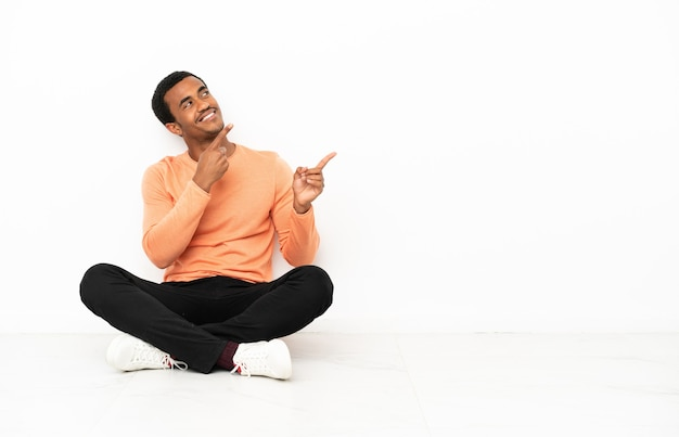 Afro-amerikaanse man zittend op de vloer over geïsoleerde copyspace-achtergrond wijzend met de wijsvinger een geweldig idee