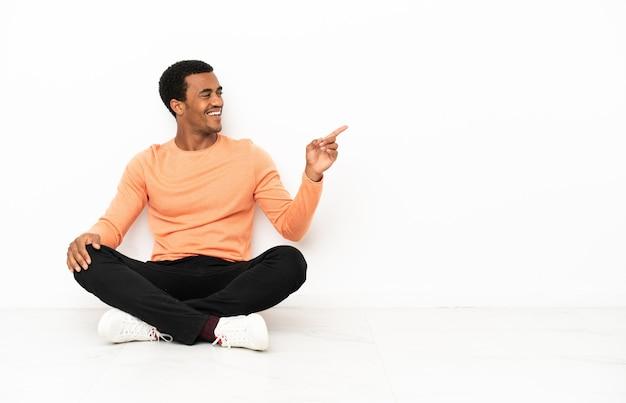 Afro-amerikaanse man zittend op de vloer over geïsoleerde copyspace-achtergrond wijzende vinger naar de zijkant en presenteren van een product