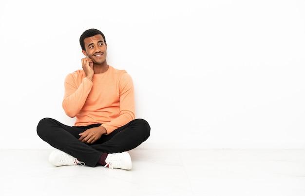 Afro-amerikaanse man zittend op de vloer over geïsoleerde copyspace-muur en denkt aan een idee terwijl hij omhoog kijkt