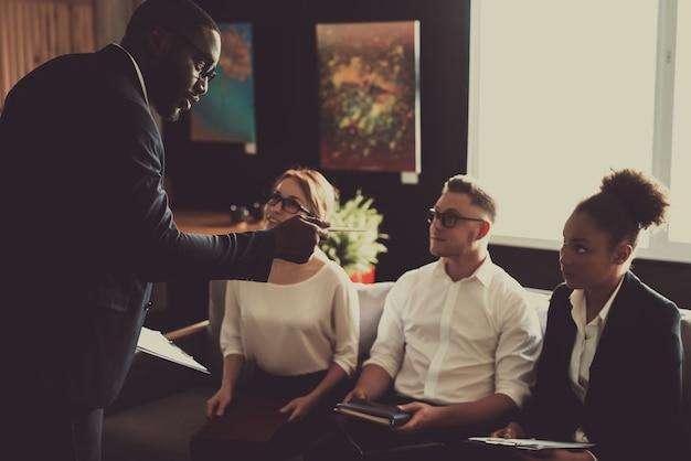 Afro-amerikaanse manager vertelt team business idea in office.