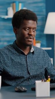 Afro-amerikaanse manager werkt thuis, drinkt koffie en typt op de computer