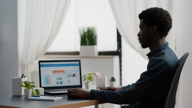 Afro-amerikaanse manager werkt vanuit huis, analyseert grafieken met verkoop en inkomen, werkt op afstand op laptop vanuit woonkamer. zwarte kerel computergebruiker met behulp van zakelijke internet online webcommunicatie