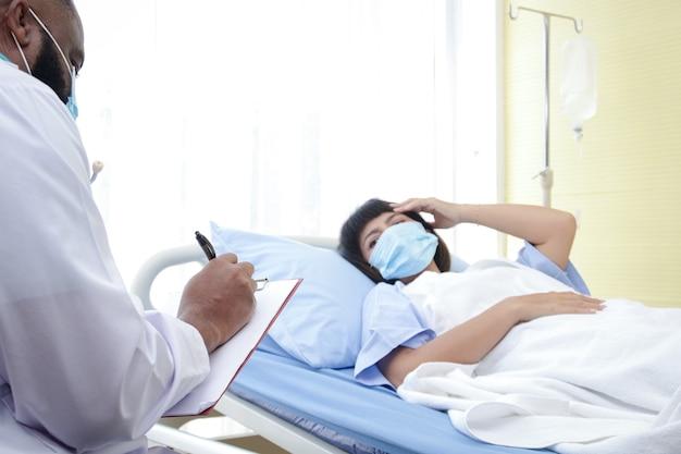 Afro-amerikaanse mannelijke arts controleer de ziekte van een vrouw die in een ziekenhuisbed ligt. behandeling van patiënten tijdens de coronavirusepidemie. concept van medische dienst.
