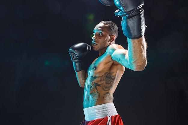 Afro-amerikaanse mannelijke bokser. jonge man bokstraining in een fitnessclub. gespierde sterke man op zwarte achtergrond studio