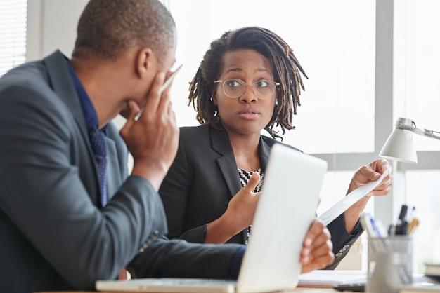 Afro-amerikaanse mannelijke en vrouwelijke collega's in pakken praten in het kantoor