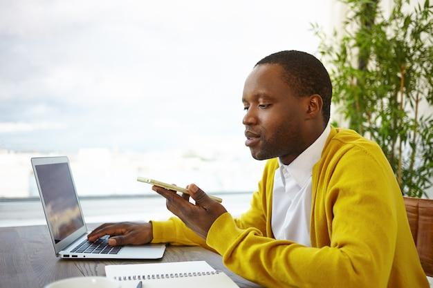 Afro-amerikaanse mannelijke freelancer zit door groot raam in de lobby van het hotel met behulp van draadloze internetverbinding, op afstand werken op laptop en spraakbericht verzenden via online app op mobiele telefoon