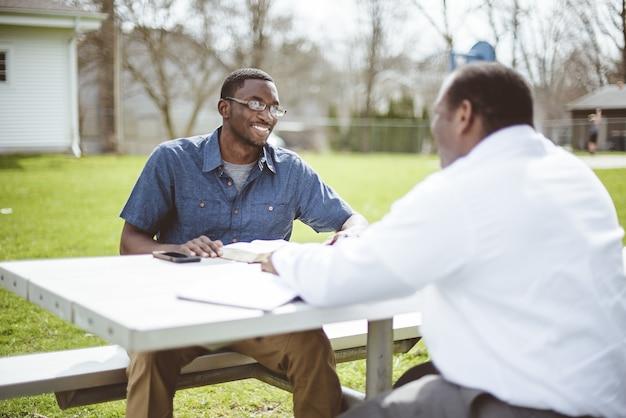 Afro-amerikaanse mannelijke vrienden zitten aan de tafel en lezen de bijbel aan tafel