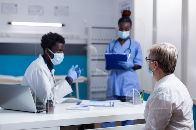 Afro-amerikaanse medisch team in gesprek met senior vrouw