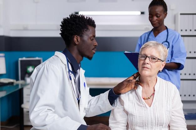 Afro-amerikaanse medische staf die senior vrouw raadpleegt