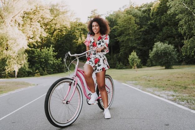 Afro-amerikaanse meisje drinkt water uit de fles op de fiets.
