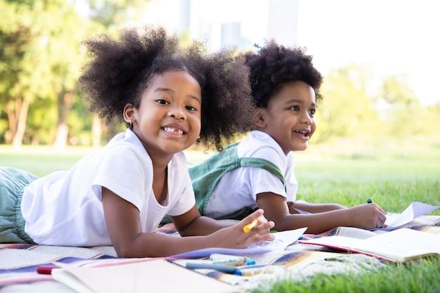 Afro-amerikaanse meisje en jongen tekenen en schilderen in het park. ze gebruiken hun verbeeldingskracht en creativiteit in kunst ideeën leren buiten de klas