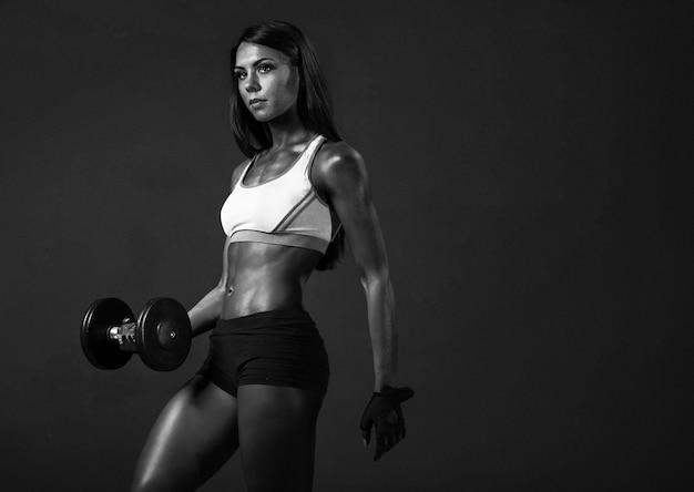 Afro-amerikaanse meisje fitness trainer met halters doen oefeningen