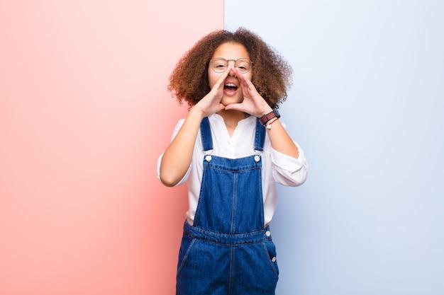 Afro-amerikaanse meisje gelukkig, opgewonden en positief gevoel, het geven van een grote schreeuw met handen naast de mond, uitroepen tegen vlakke muur