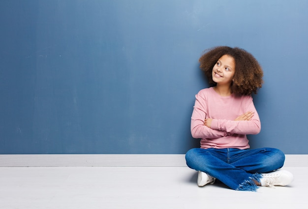 Afro-amerikaanse meisje gelukkig, trots en hoopvol voelen, zich afvragen of denken, opzoeken om ruimte te kopiëren met gekruiste armen zittend op de vloer