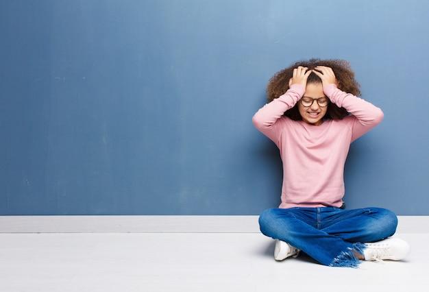 Afro-amerikaanse meisje gestrest en angstig, depressief en gefrustreerd met hoofdpijn gevoel, beide handen op te heffen zittend op de vloer