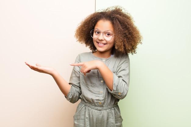 Afro-amerikaanse meisje glimlachend vrolijk en wijst naar kopie ruimte op de palm aan de zijkant, een object tegen een vlakke muur tonen of adverteren
