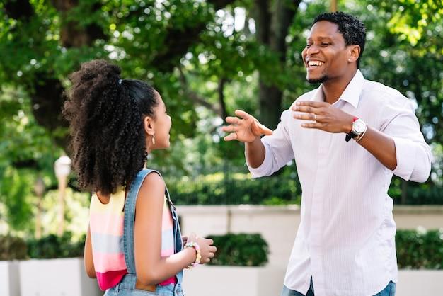 Afro-amerikaanse meisje met haar vader met een goede tijd samen buiten op straat.