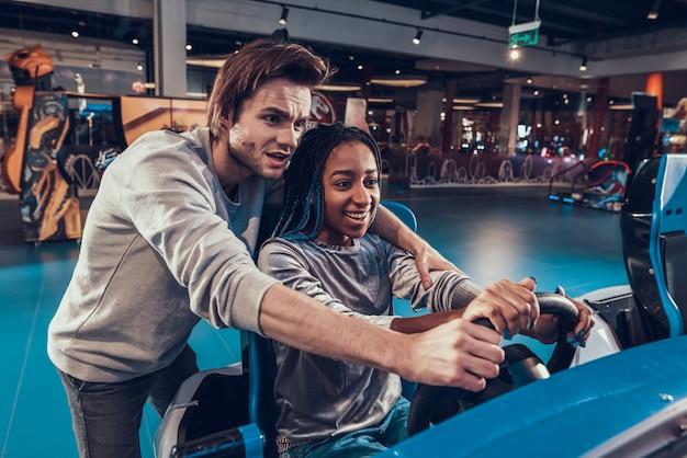 Afro-amerikaanse meisje rijden auto in arcade.