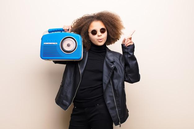 Afro-amerikaanse meisje tegen platte muur luisteren muziek met een ouderwetse radio