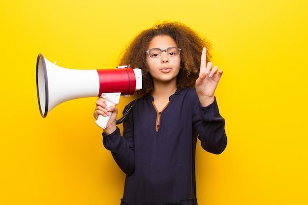 Afro-amerikaanse meisje tegen platte muur met een megafoon