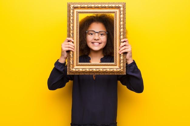 Afro-amerikaanse meisje tegen vlakke muur met een barok frame