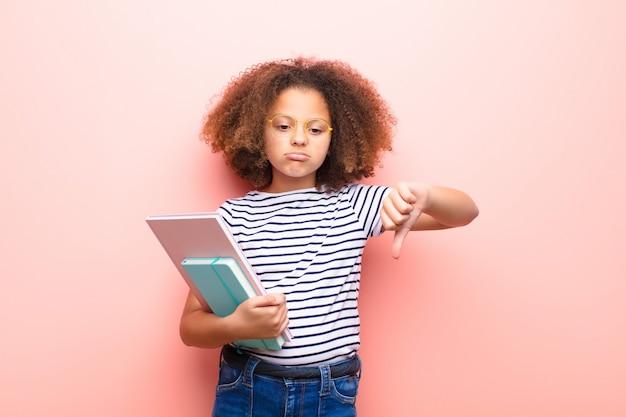 Afro-amerikaanse meisje tegen vlakke muur met een boek