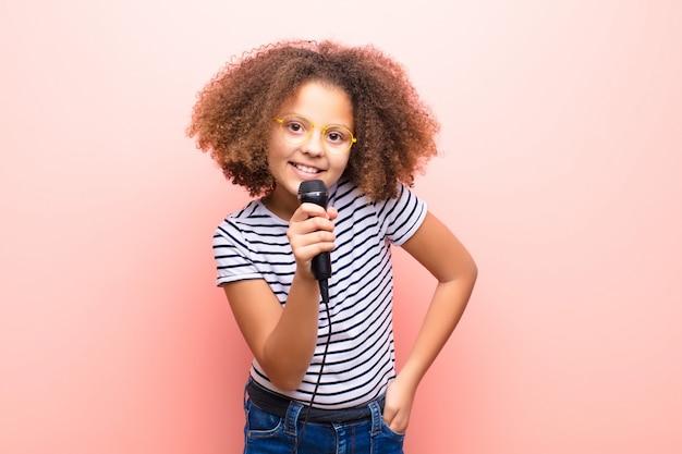 Afro-amerikaanse meisje tegen vlakke muur met een microfoon