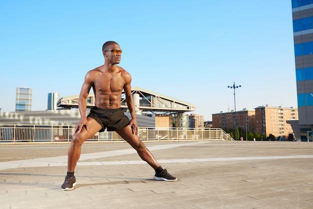 Afro-amerikaanse mens die het uitrekken in stedelijk milieu doet zich