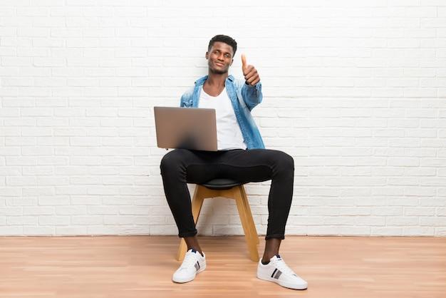 Afro-amerikaanse mens die met zijn laptop werkt die duimen op gebaar en het glimlachen geeft