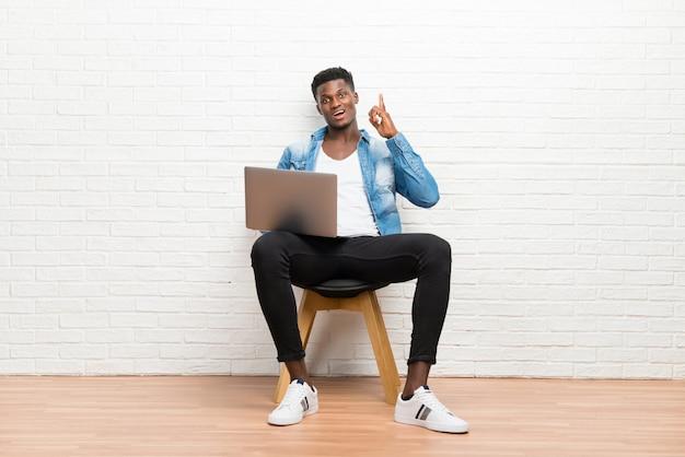 Afro amerikaanse mens die met zijn laptop werkt die en een idee bevindt zich denkt