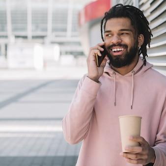 Afro-amerikaanse mens die op telefoon lacht