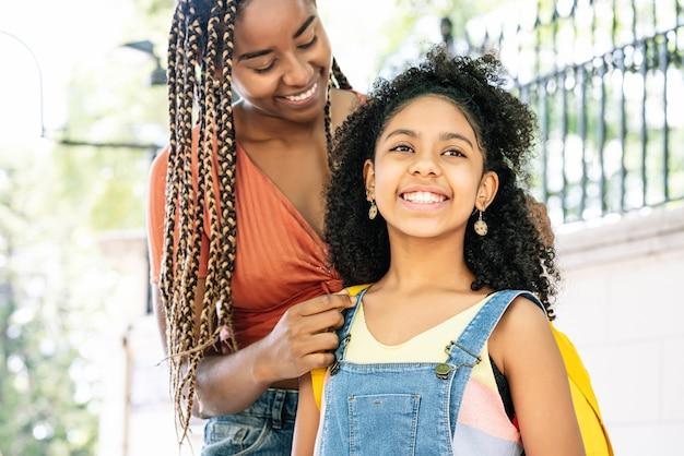 Afro-amerikaanse moeder die haar dochter naar school brengt. onderwijsconcept.