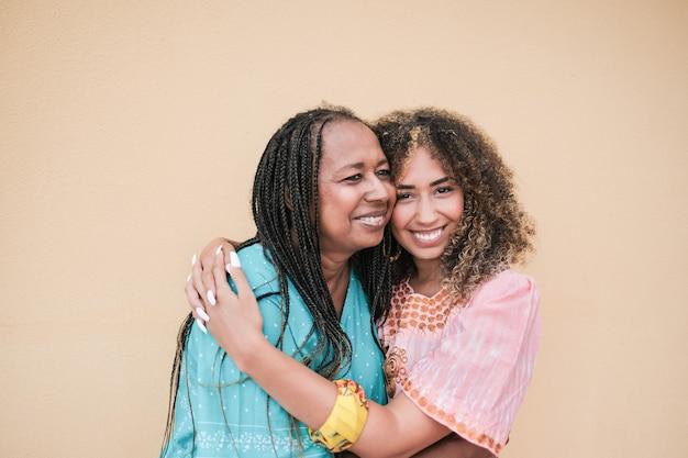 Afro-amerikaanse moeder die haar volwassen dochter van gemengd ras knuffelt - familieliefde