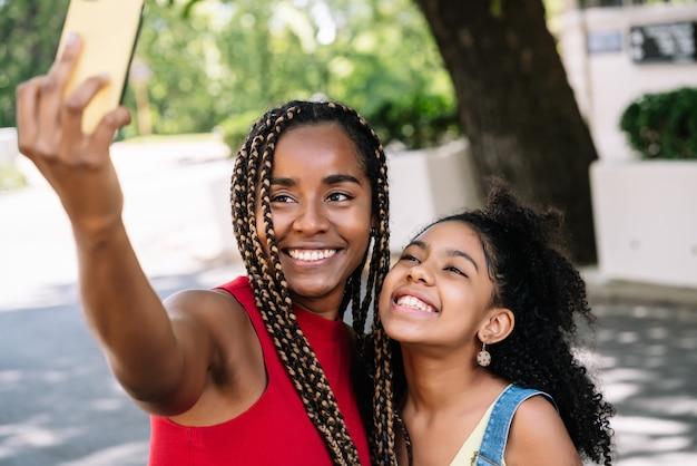Afro-amerikaanse moeder en dochter genieten van een dag buiten terwijl ze een selfie met een mobiele telefoon op straat nemen