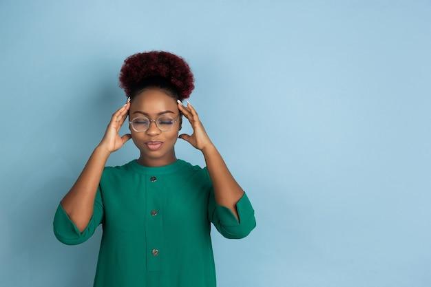 Afro-amerikaanse mooie jonge vrouw portret op blauwe muur emotioneel en expressief