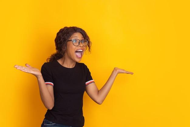 Afro-amerikaanse mooie jonge vrouw portret op gele studio achtergrond emotioneel en expressief