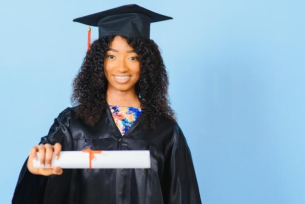 Afro-amerikaanse mooie vrouw in een zwart gewaad en hoed, op een blauwe geïsoleerde achtergrond glimlacht.