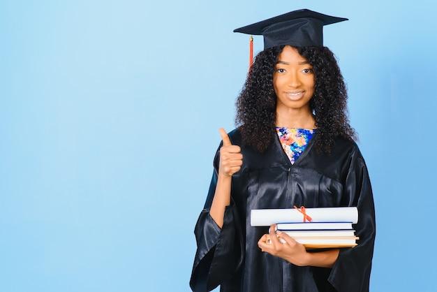 Afro-amerikaanse mooie vrouw in een zwarte mantel en hoed, op een blauwe achtergrond geïsoleerd glimlacht.