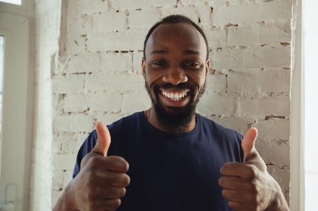 Afro-amerikaanse muzikant op witte bakstenen muur achtergrond, vrolijk en gelukkig.