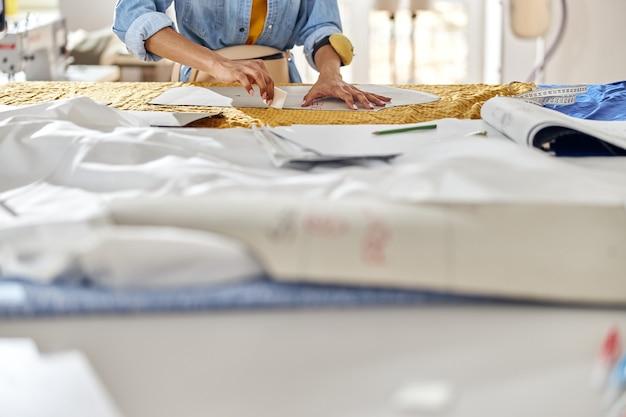 Afro-amerikaanse naaister tekent patroon op stof met kleermakerskrijt aan grote snijtafel