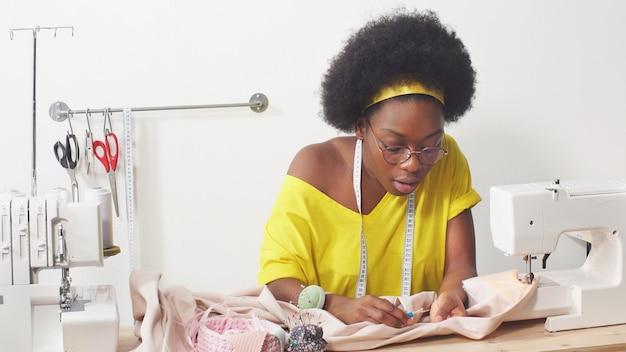 Afro-amerikaanse naaister werkt op haar favoriete baan en naait kleding in haar naaiatelier.
