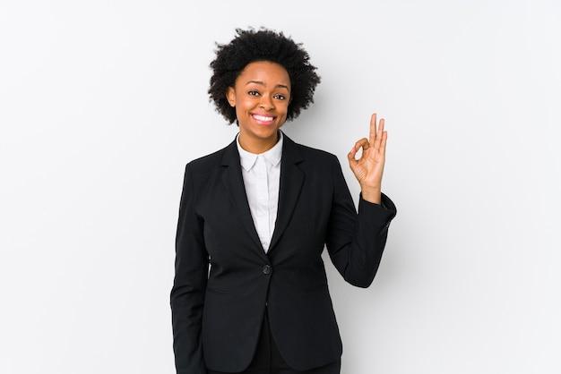 Afro-amerikaanse onderneemster van middelbare leeftijd vrolijk en vol vertrouwen met ok gebaar.