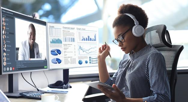Afro-amerikaanse ondernemer die in koptelefoons praat met haar collega's in videoconferentie. multi-etnisch business team werkt vanuit kantoor met behulp van pc en bespreekt het financiële rapport van hun bedrijf.