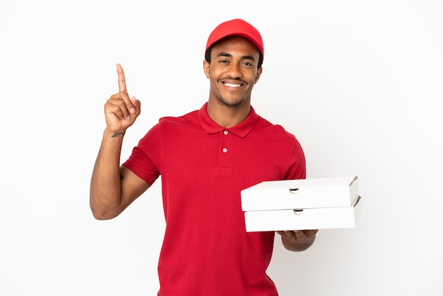 Afro-amerikaanse pizzabezorger die pizzadozen ophaalt over een geïsoleerde witte muur die een geweldig idee naar boven wijst