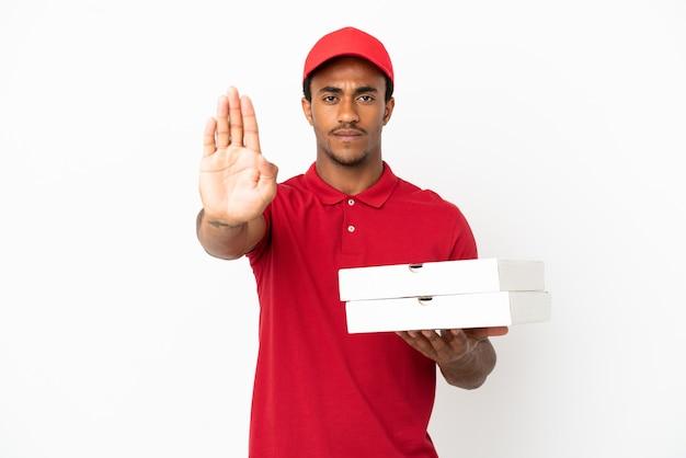 Afro-amerikaanse pizzabezorger die pizzadozen ophaalt over een geïsoleerde witte muur die een stopgebaar maakt