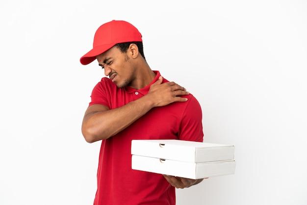 Afro-amerikaanse pizzabezorger die pizzadozen ophaalt over een geïsoleerde witte muur die lijdt aan pijn in de schouder omdat hij moeite heeft gedaan