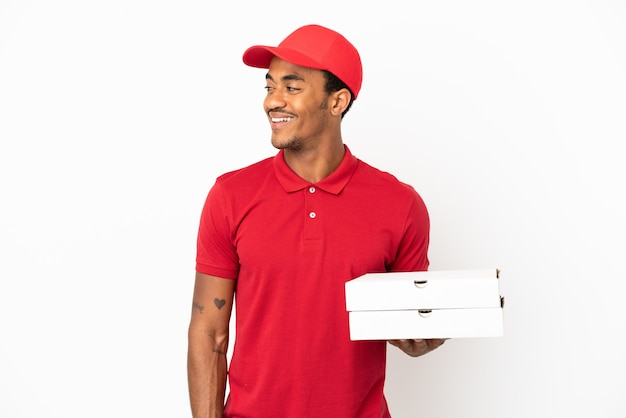 Afro-amerikaanse pizzabezorger die pizzadozen ophaalt over een geïsoleerde witte muur die naar de zijkant kijkt