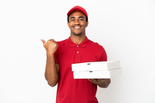 Afro-amerikaanse pizzabezorger die pizzadozen ophaalt over een geïsoleerde witte muur die naar de zijkant wijst om een product te presenteren