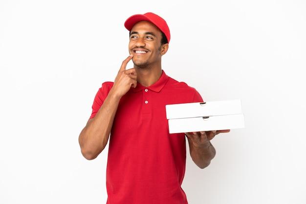 Afro-amerikaanse pizzabezorger die pizzadozen ophaalt over een geïsoleerde witte muur die twijfelt terwijl hij opkijkt