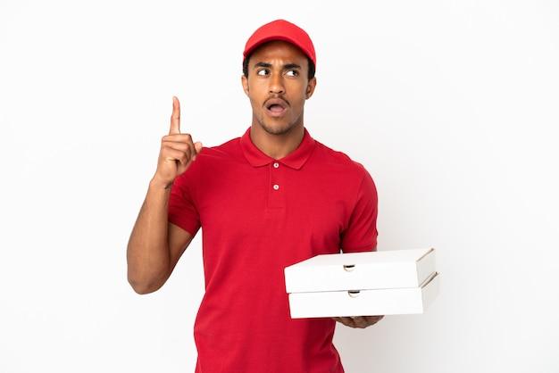 Afro-amerikaanse pizzabezorger die pizzadozen ophaalt over een geïsoleerde witte muur en denkt aan een idee met de vinger omhoog